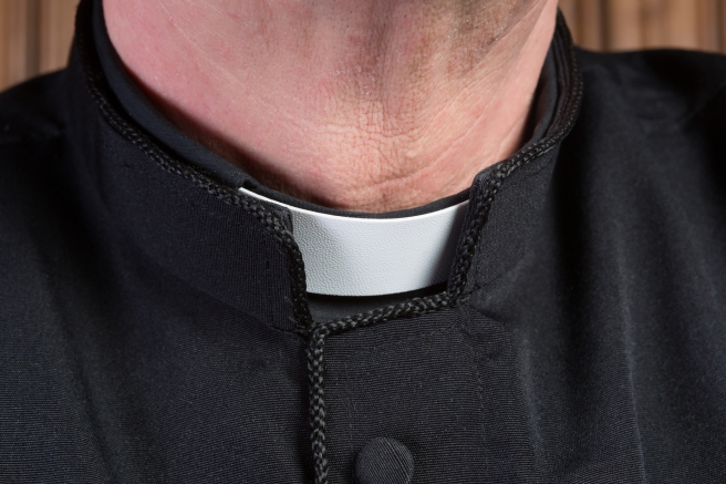 Closeup of the neck of a priest wearing a black shirt with cassock and white clerical collar